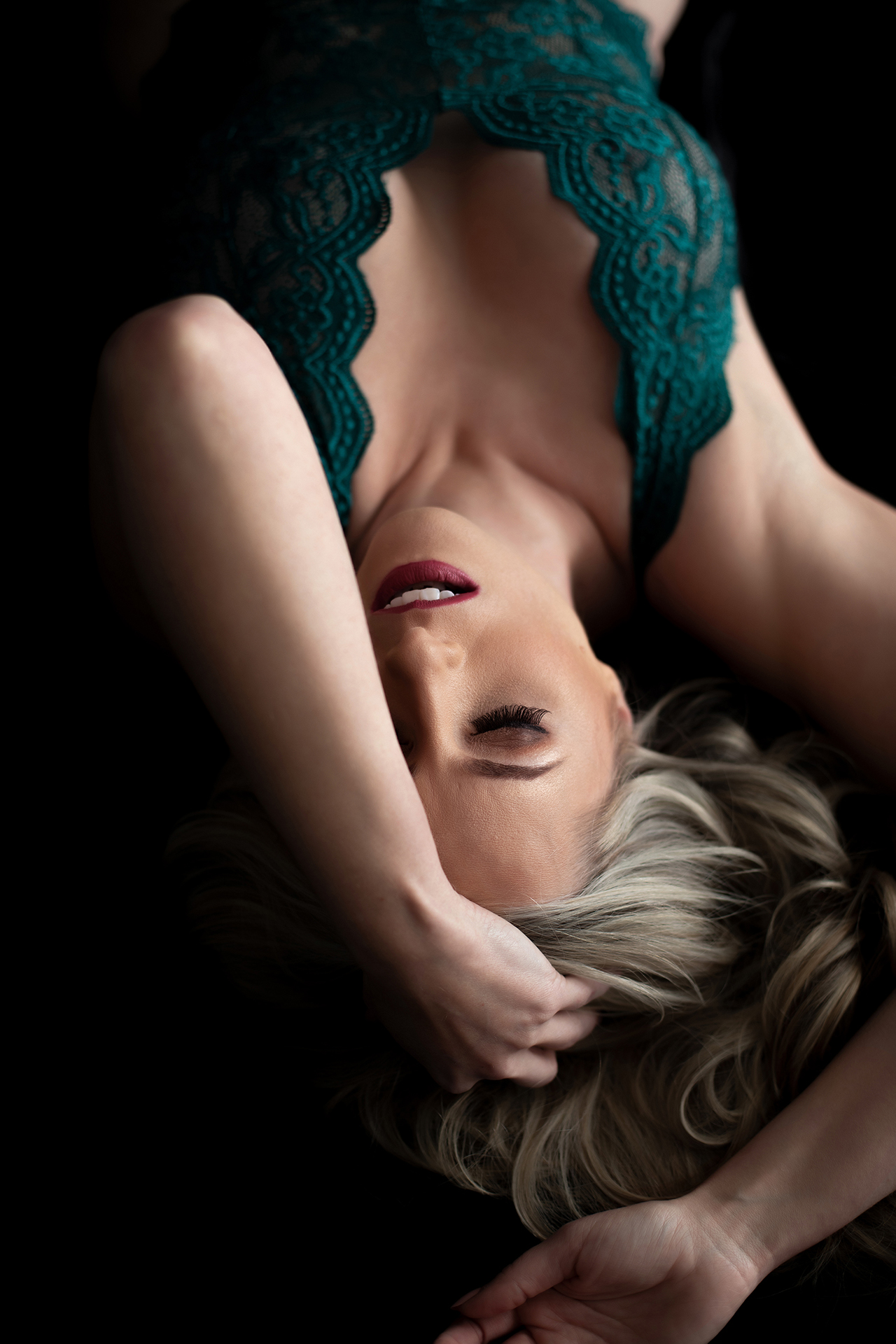 Boudoir Pose with forearm covering half of face, featuring blonde in emerald bodysuit.