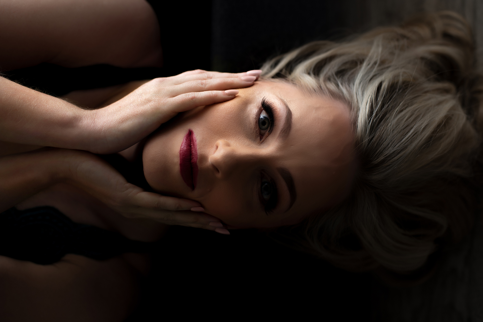 Boudoir pose featuring blonde touching her face.